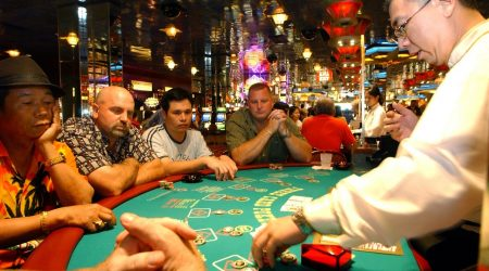 **CORRECTS TO CLARIFY SECOND SENTENCE REMOVES INFORMATION ABOUT CASINOS CLOSING WEDNESDAY **Dealer Patrick Chen collects chips on the poker table as players  look on at the Resorts Atlantic City casino in Atlantic City, N.J., Tuesday, July 4, 2006. Gov. Jon S. Corzine hauled lawmakers in to work on the July Fourth holiday, imploring them to end a budget standoff that has shut down many government services, while Atlantic City casinos fought to keep from being dragged into the dispute. (AP Photo/Mary Godleski)